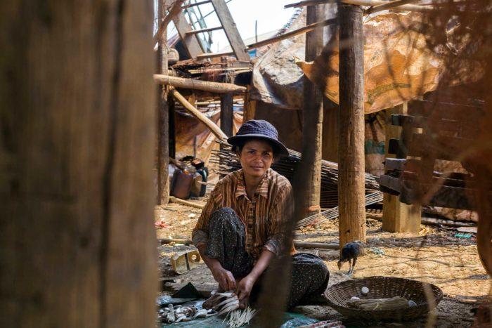 79-woman-cleaning-fish,-kompong-khleang-cambodia